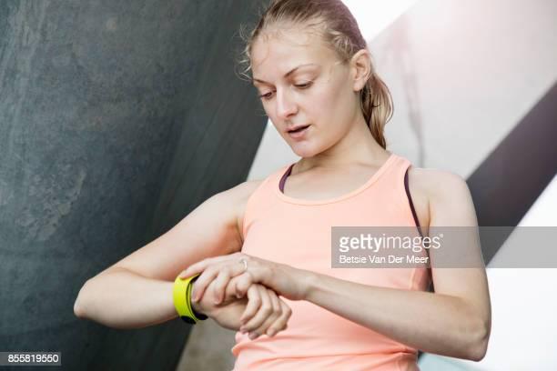 Female runner checks her fitness tracker, standing in urban area in city.