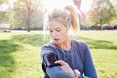 female runner checks phone in armband