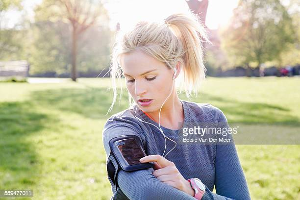 female runner checks phone in armband