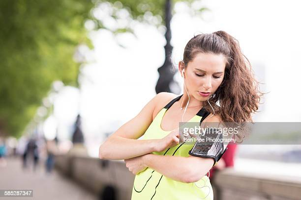 Female runner choosing music on smartphone armband at riverside