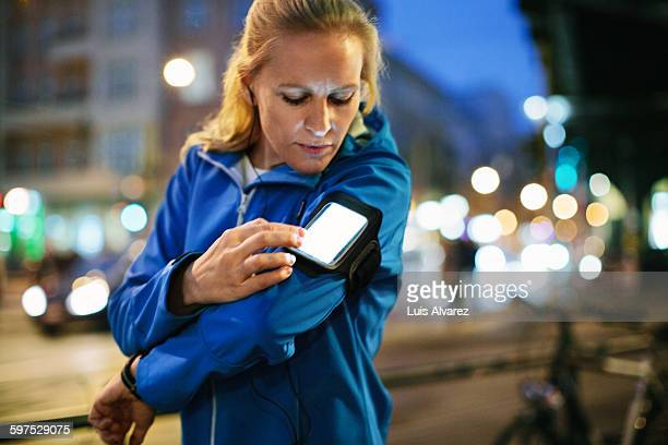 Female runner choosing music on smartphone