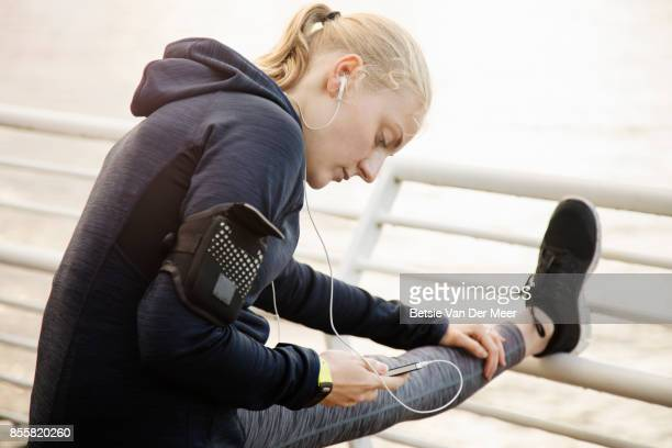 Female runner doing stretches while looking at mobile phone.