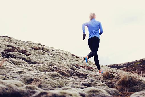 Female runner glides across grassy hillside