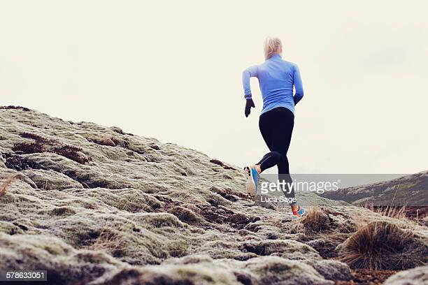 Female runner glides across grassy hillside