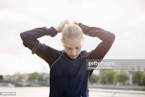 Female runner is adjusting her hair, preparing for run in urban city.
