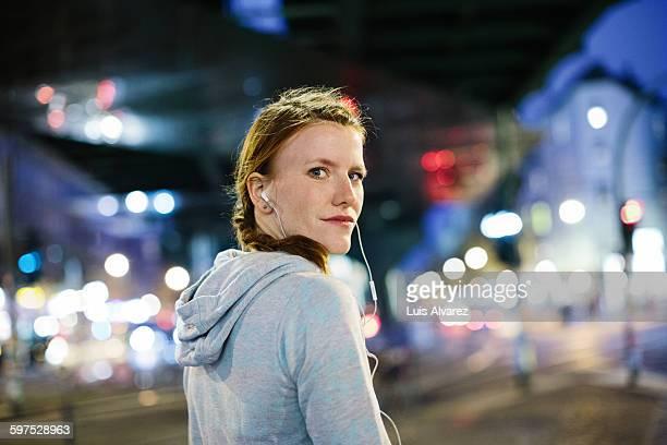 Female runner listening music on city street