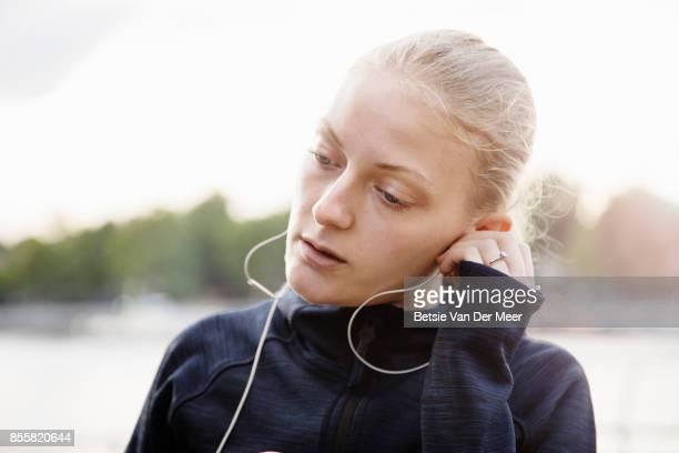 Female runner listens to music on headphone.