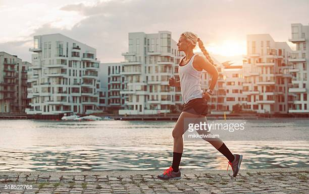 Female runner on the move as sun sets in city