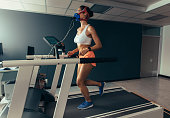 Female runner with mask running on treadmill machine testing her performance. Woman athlete examining her fitness in biomechanics lab.