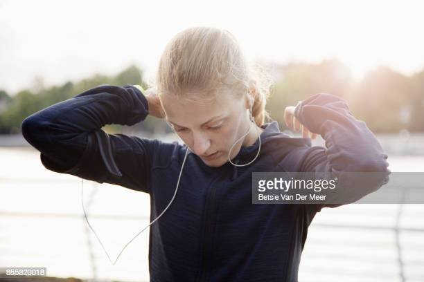 Female runner places hood of her sports running top down, preparing for run.