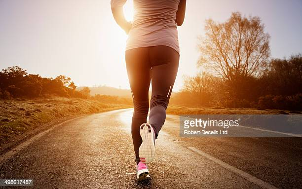 Female runner running along road