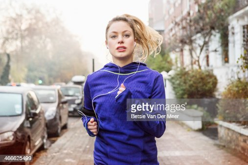 Female runner running down urban street.