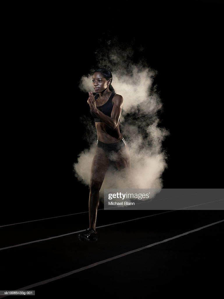Female runner running in cloud of smoke, studio shot : Stock Photo