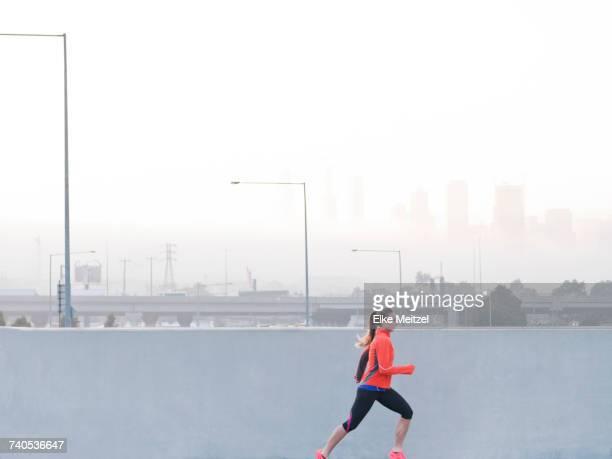 Female runner running in misty morning cityscape, Melbourne, Australia