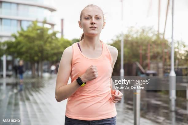 Female runner running through urban area in city.