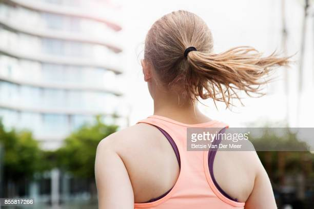 Female runner runs in city, photographed from behind.