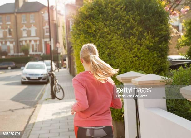 Female runner runs in residential street, in city.