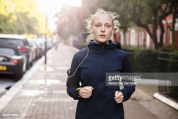 Female runner runs in urban residential street.