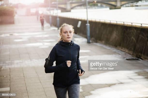 Female runner runs on riverside path in city.