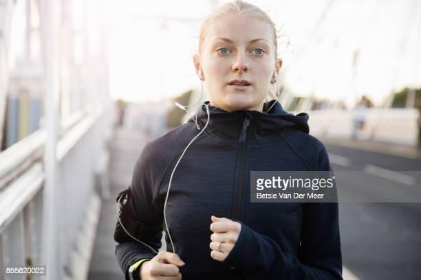 Female runner runs on urban bridge in city.