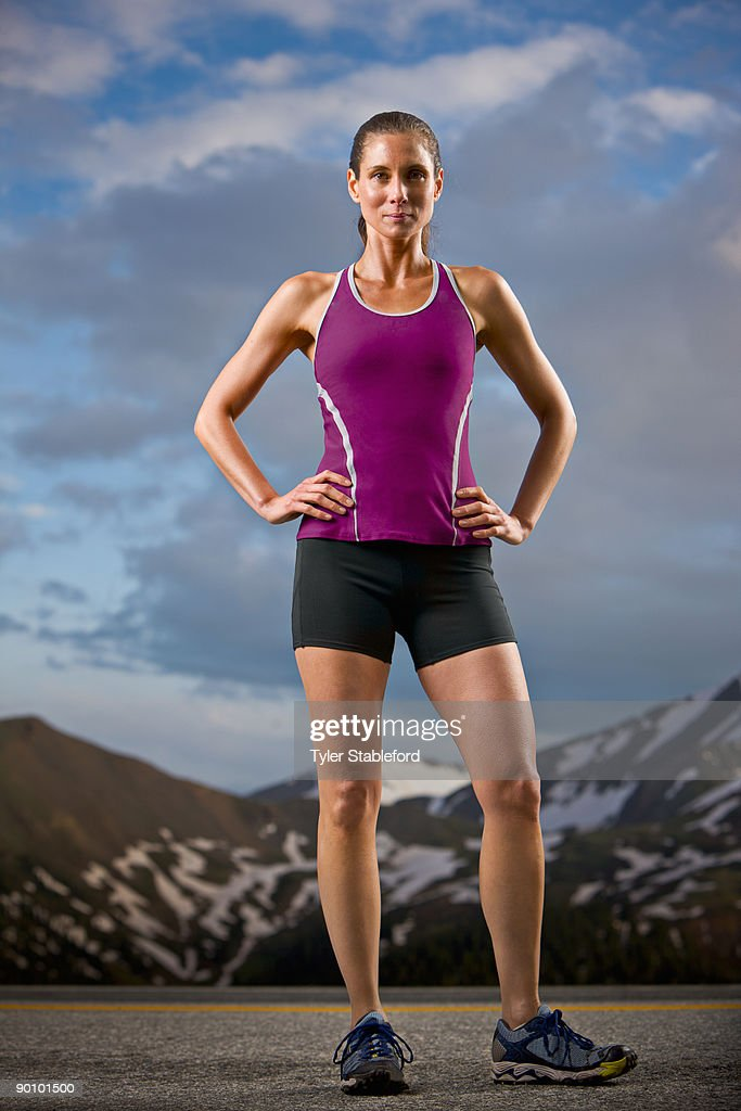 A female runner stands confidently on a road.