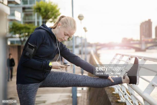 Female runner stretches leg, while checking mobile phone at riverside.