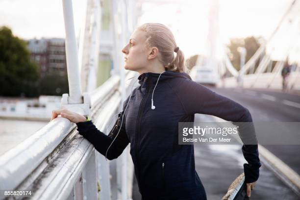 Female runner stretches muscles, standing on urban bridge in city.