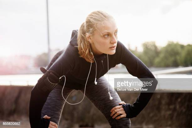 Female runner stretches while resting at river side in city.