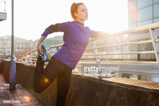 female runner stretching leg in urban space.