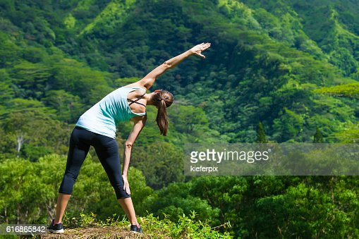Female runner stretching outdoors : Stock Photo