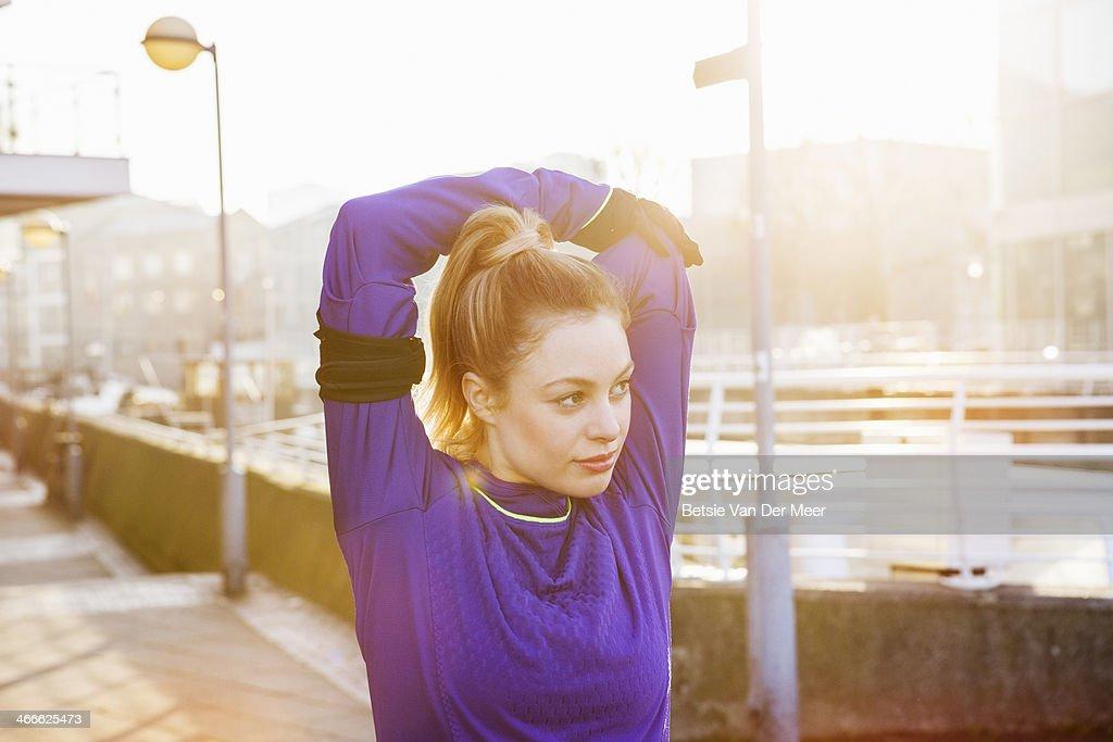 Female runner stretching shoulders on street.