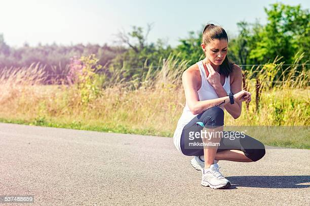 Female runner takes a break and measure pulse
