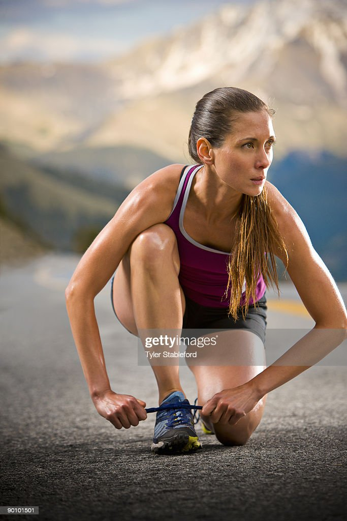 A female runner ties her shoes on a road. : Stock Photo