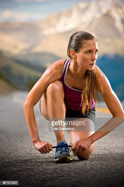 A female runner ties her shoes on a road.