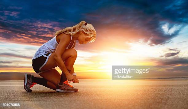 Female runner ties shoe before going for a run