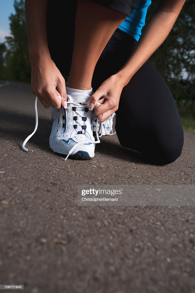 Female runner tying her shoelace : Stock Photo