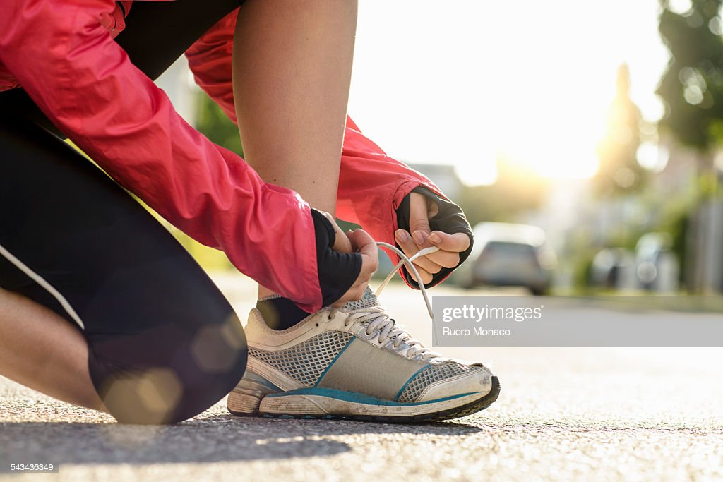 female runner tying shoe lace in a urban area : Stock Photo