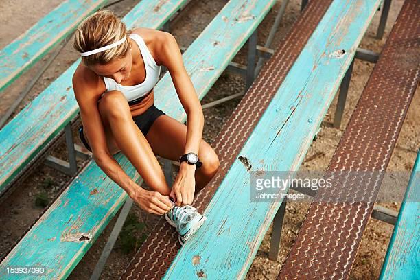 Female runner tying shoe