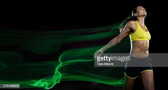 female runner winning race with light trails
