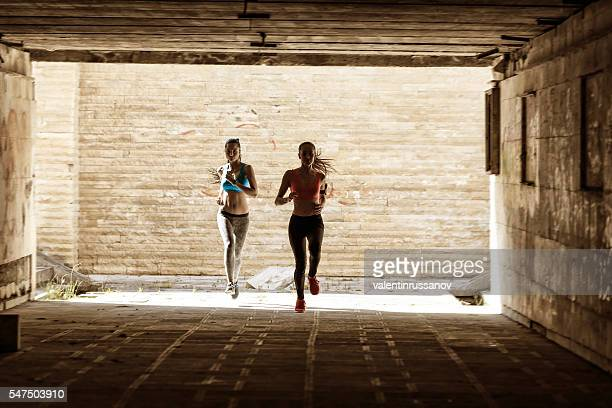 Female runners jogging in underpass