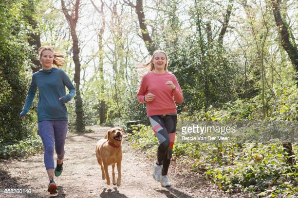 Female runners running with pet dog in forest.