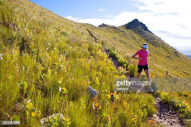 Femme courir à fond sur un sentier de montagne.