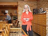 Female sales clerk standing in eyeglass store, portrait, customer in background