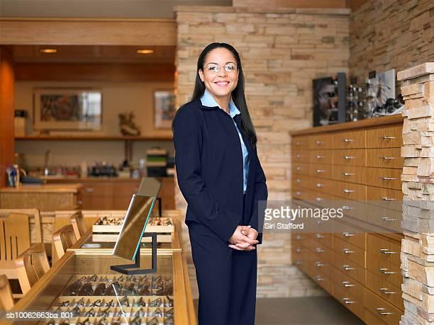 Female sales clerk standing in eyeglass store, portrait