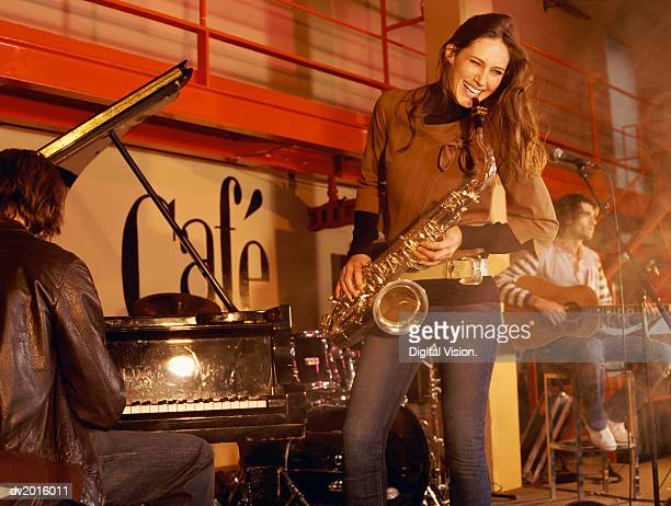 Female Saxophonist Performs on Stage With a Pianist and Guitarist