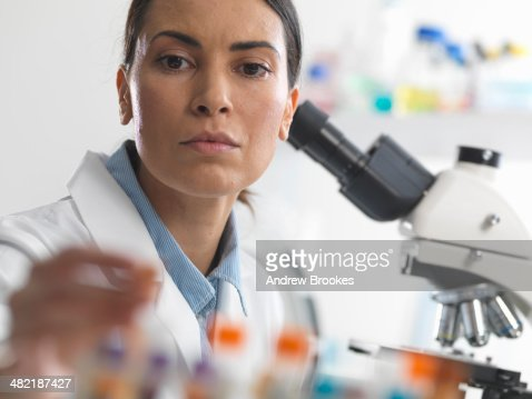 Female scientist about to view a blood sample under a microscope
