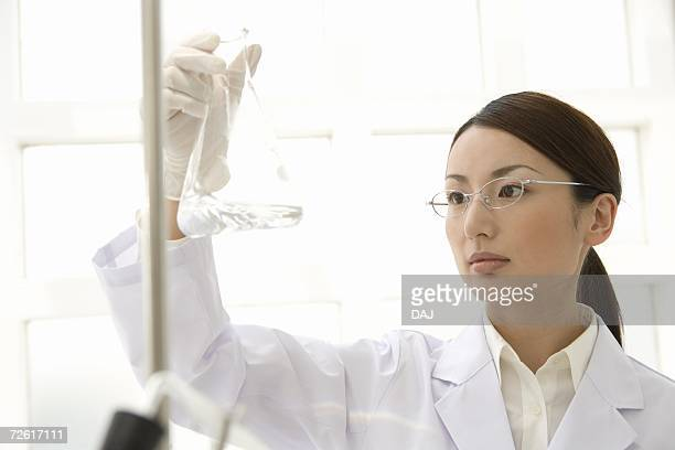 Female scientist holding up and watching a conical flask, front view, differential focus