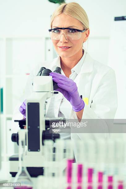 Female scientist in front of a microscope.