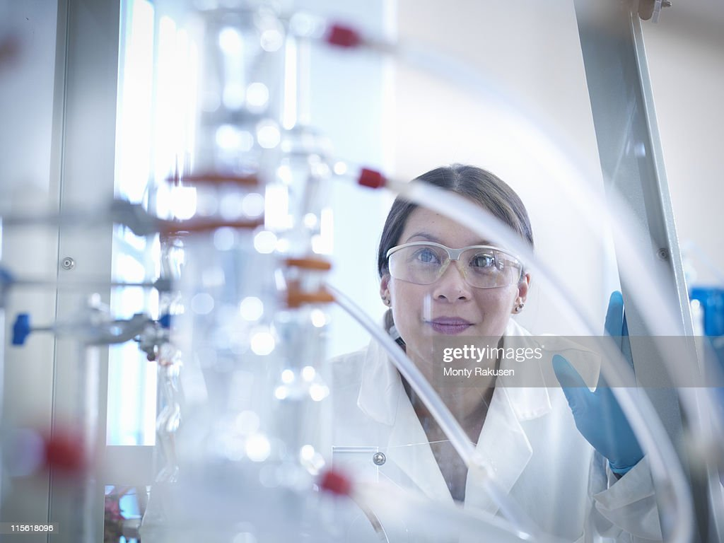 Female scientist looking at equipment in fume cupboard in laboratory : Stock Photo