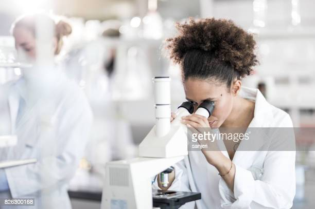 Female Scientist Looking Through Microscope